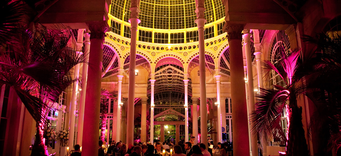 Beautifully-lit-in-yellow-and-pink-wedding-reception-at-Syon-Park-a-unique-wedding-venue-in-Middlesex-near-London-featured-on-the-Gay-Wwedding-Guide