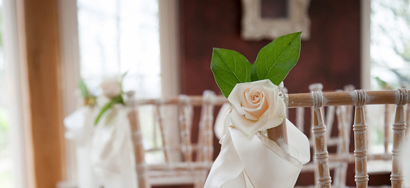 Yorkshire-gaye-wedding-venue-rose-on-chair-in-Yorkshire-Dales-at-Yorebridge-House-via-the-Gay-Wedding-Guide-image-copyright-TomArber