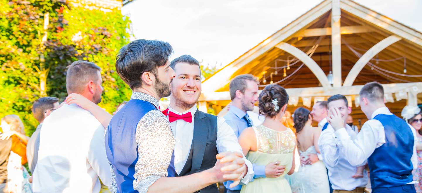 Two-Grooms-dancing-at-Balmer-Lawn-Gay-wedding-venue-Brockenhurst-via-the-Gay-Wedding-Guide
