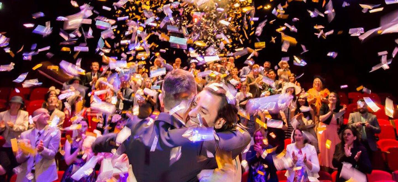 Confetti falls at gay wedding held at REP Theatre wedding venue Birmingham unique wedding venue via the Gay Wedding Guide