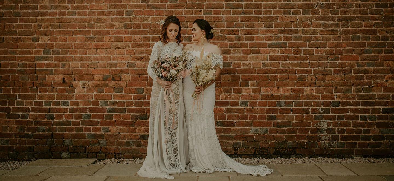 lesbian brides outside wall at Brickhouse Vineyard unique wedding venue devon via The Gay Wedding Guide