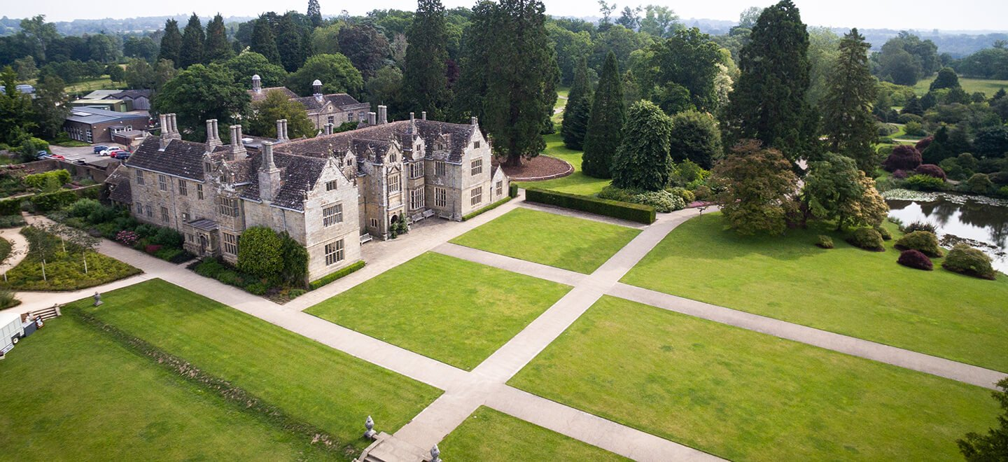aerial view of manshion at wakehurst gay wedding venue west sussex via gay wedding guide 1440x660 1 1