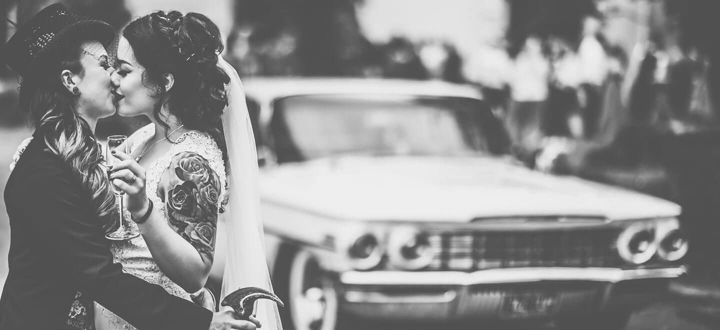 lesbian brides kiss infront of vintage car at lesbian wedding image by gay wedding photographer GRW Photography1 6